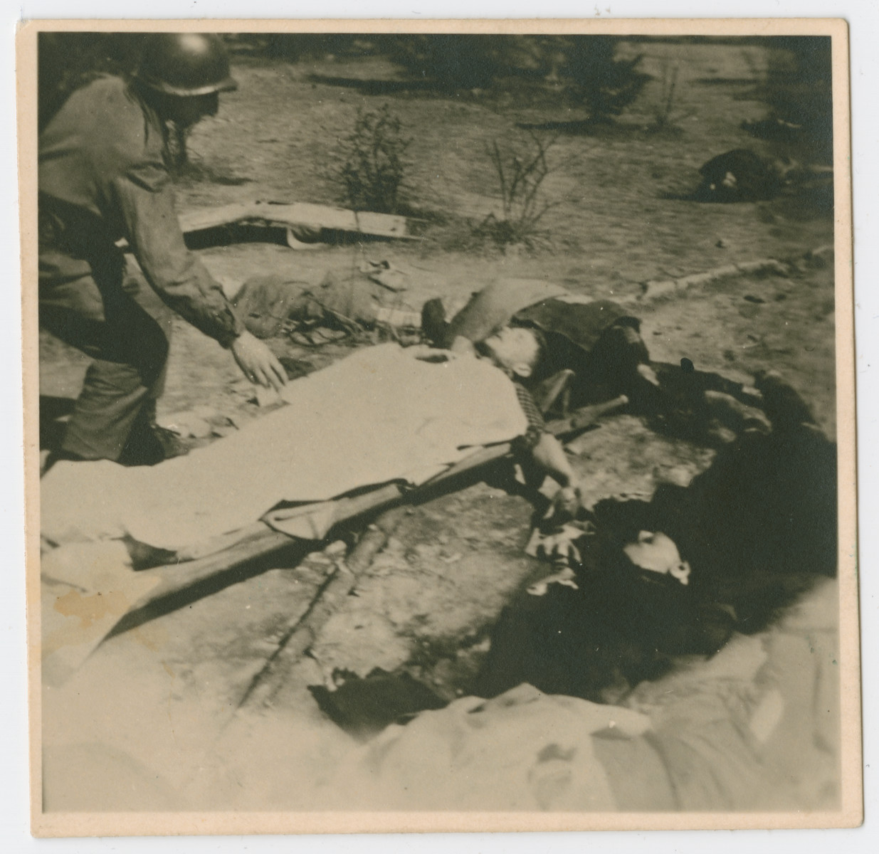 An American serviceman inspects the covered body of either a survivor or a victim lying on a stretcher on the grounds of the Ohrdruf concentration camp.