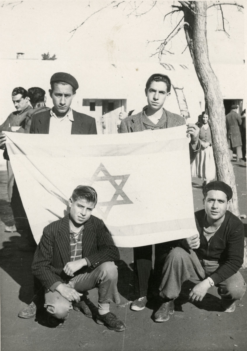 Group portrait of youth in Mahane David, an immigration camp for North African Jews en route to Israel, holding an Israeli flag.  Shimon Sousson is at the bottom right.