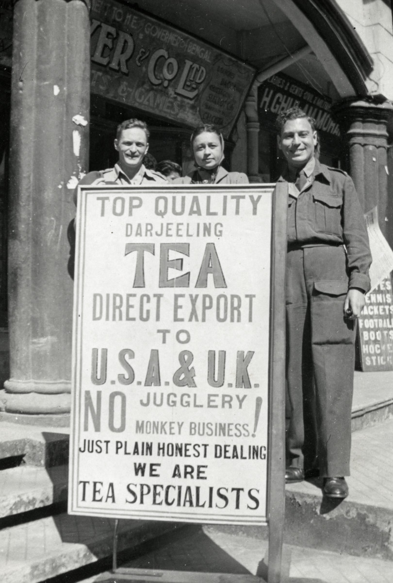 Esther Weeg and two men stand behind a sign advertising a tea business in Sonari, India.