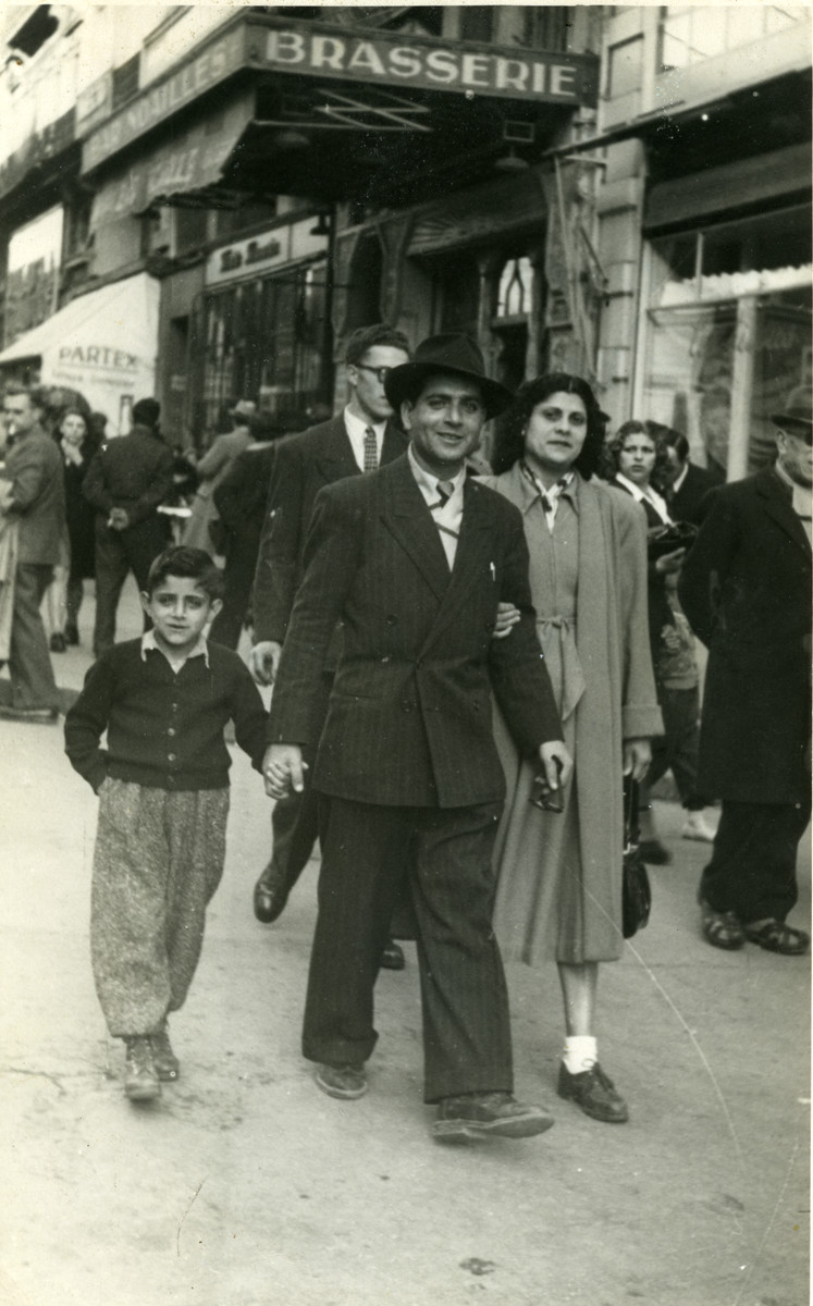 Shimon Sousson, his wife, and their son walk down a commerical street of Marseilles.
