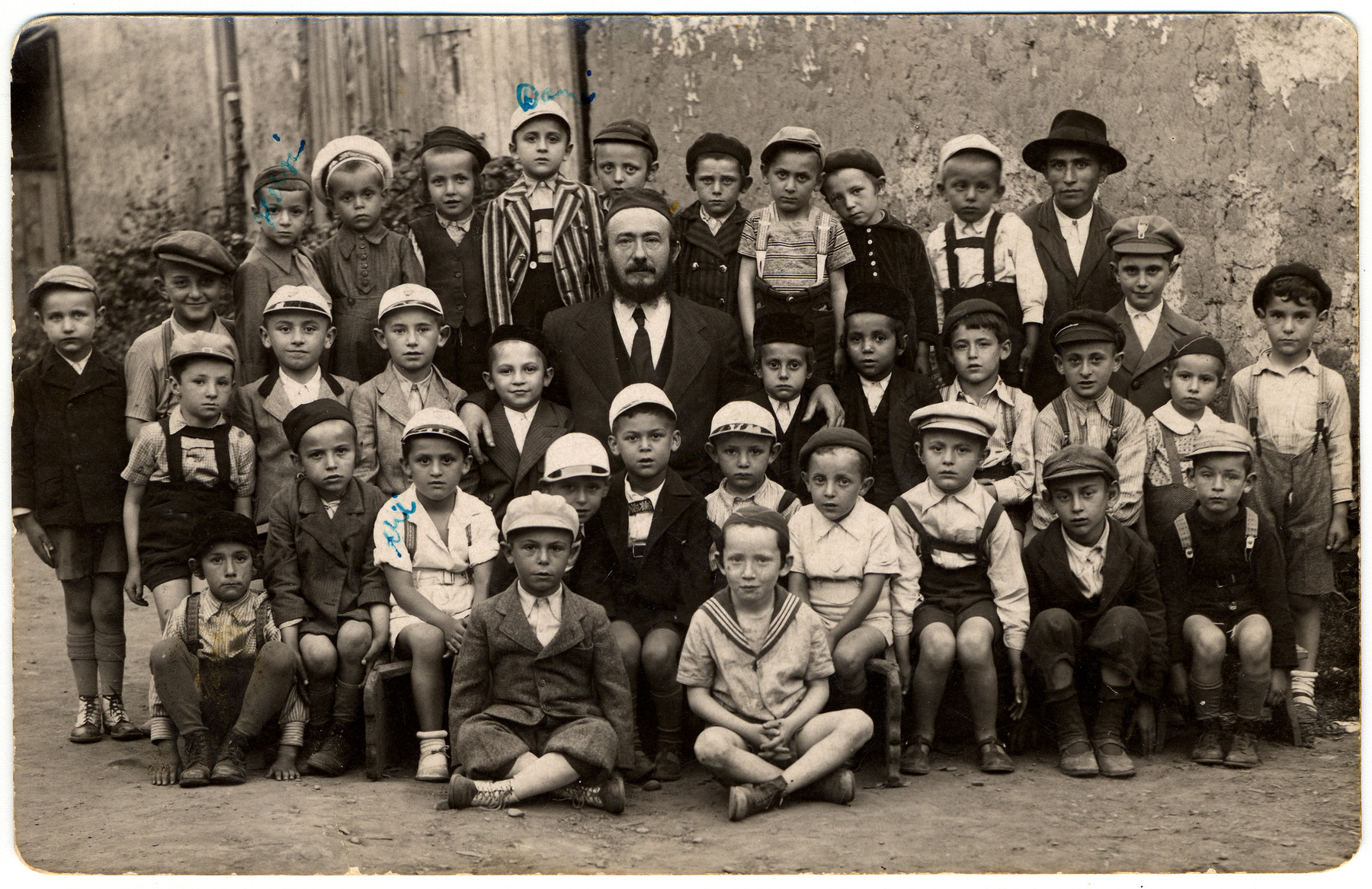 Group portrait of young boys in a cheder in Mukachevo.    Among those pictured is Aharon (Ari) Friedman (seated on the bench, second from the left).  Daniel Friedman (his cousin) is in the top row in the striped jacket.