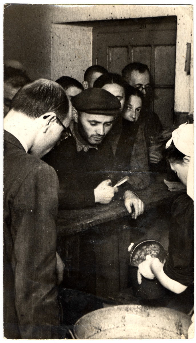 People wait for food to be distributed in one of the public kitchens of the Lodz ghetto.   The kitchen director was Leibel Fehrman.