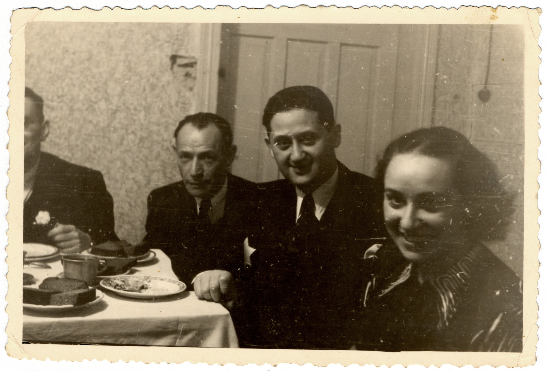 Lodz ghetto officials gather at a table for a meal.    Pictured from the left are Naftali [?], Aron Jakubowicz and Dora Fuks.