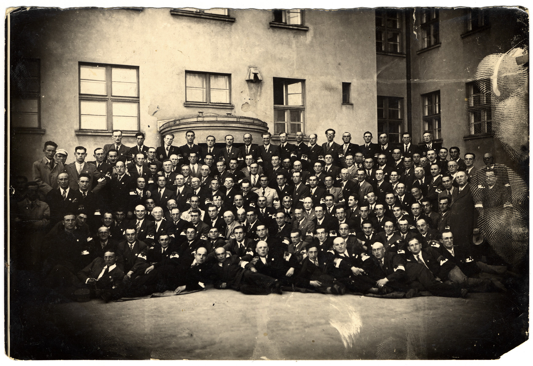 Large group portrait of members of the Lodz ghetto Jewish police.   Among those pictured, in the fourth row from the bottom, are Julek Grosbart (second from the left), Zygmunt Reingold, the commander of the police department (fourth from the left) and Leon Rozenblat, the head of the ghetto police (seventh from the left). Abram Josef (Alfred) Chimowicz is standing in the first row of standing policeman, on the very far right,