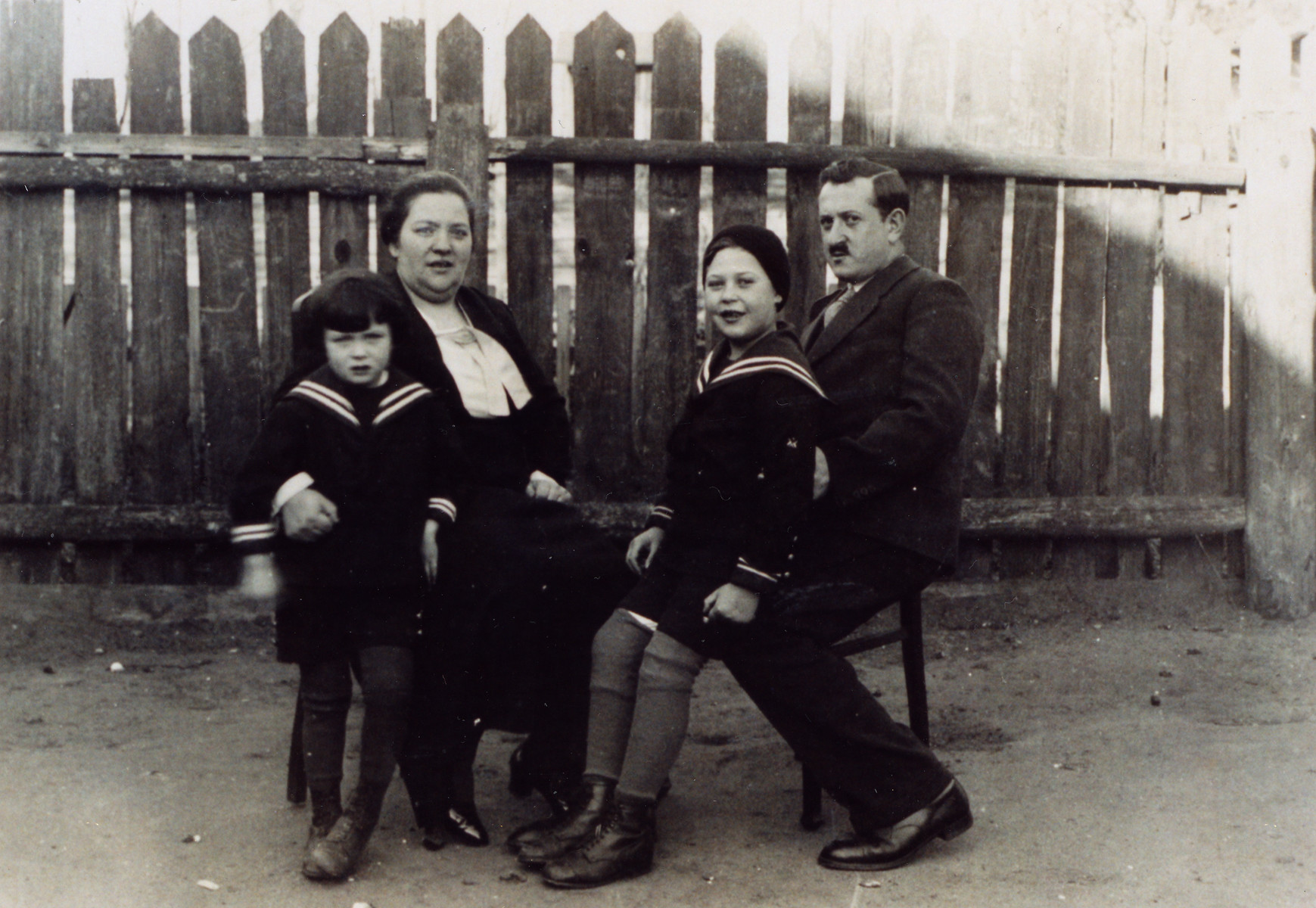 The Guth family sits outdoors in front of a wooden fence.  Pictured from left to right are Kurt, Rosa, Heinz and Felix Guth.