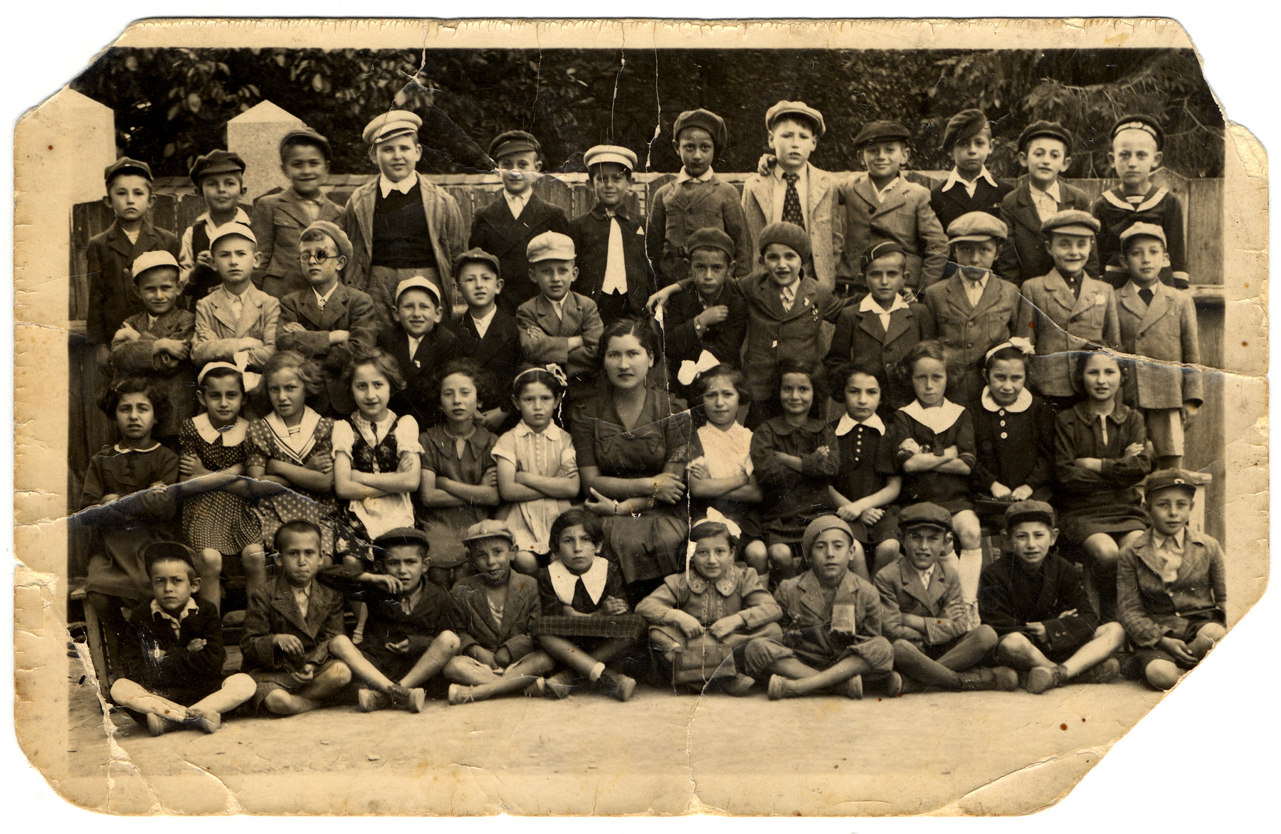 Group portrait of children in the third grade class of the Hebrew Gymnasium in Mukachevo.  Among those pictured are Ruth Friedman (second row, sixth from left) and Eugen (Tuli) Shoenfeld (top row, fifth from left).  The teacher's name was Miss Mermelstein.