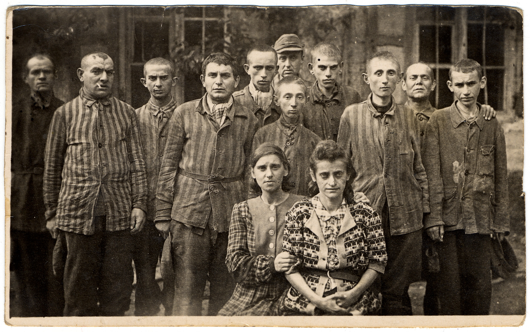 Survivors from an unidentified concentration camp, most of whom are still in uniform, pose for a group photograph.   The original Yiddish caption states that the people represented were detained with the donor's brother-in-law.    Among those pictured is Isak Lipschitz (later Isak Lips), standing third from left.