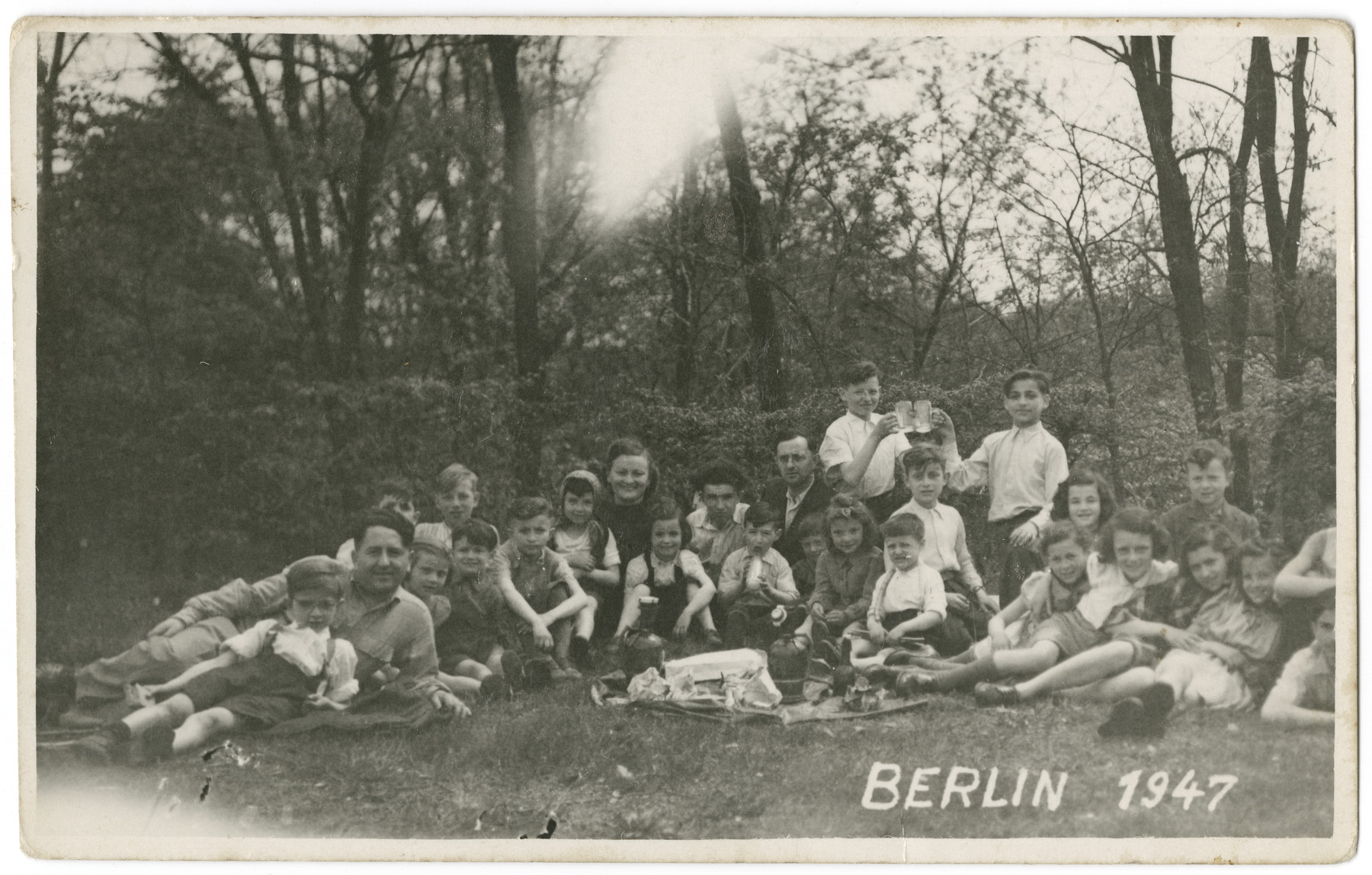 Group portrait of Jewish children and teachers from the Schlachtensee displaced persons camp on an outing to a park.  Nathan Rubinstein is in the back holding a mug.