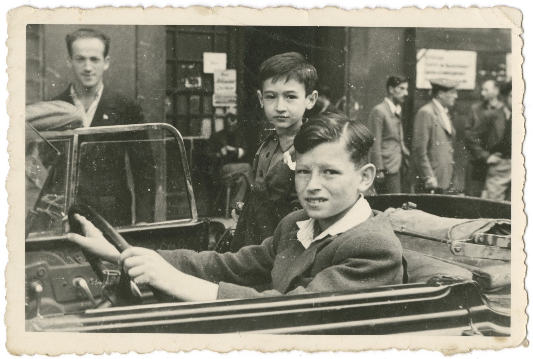 Nathan Rubinstein drives a car in the Schlachtensee displaced persons camp.  His brother Benny is standing next to him.