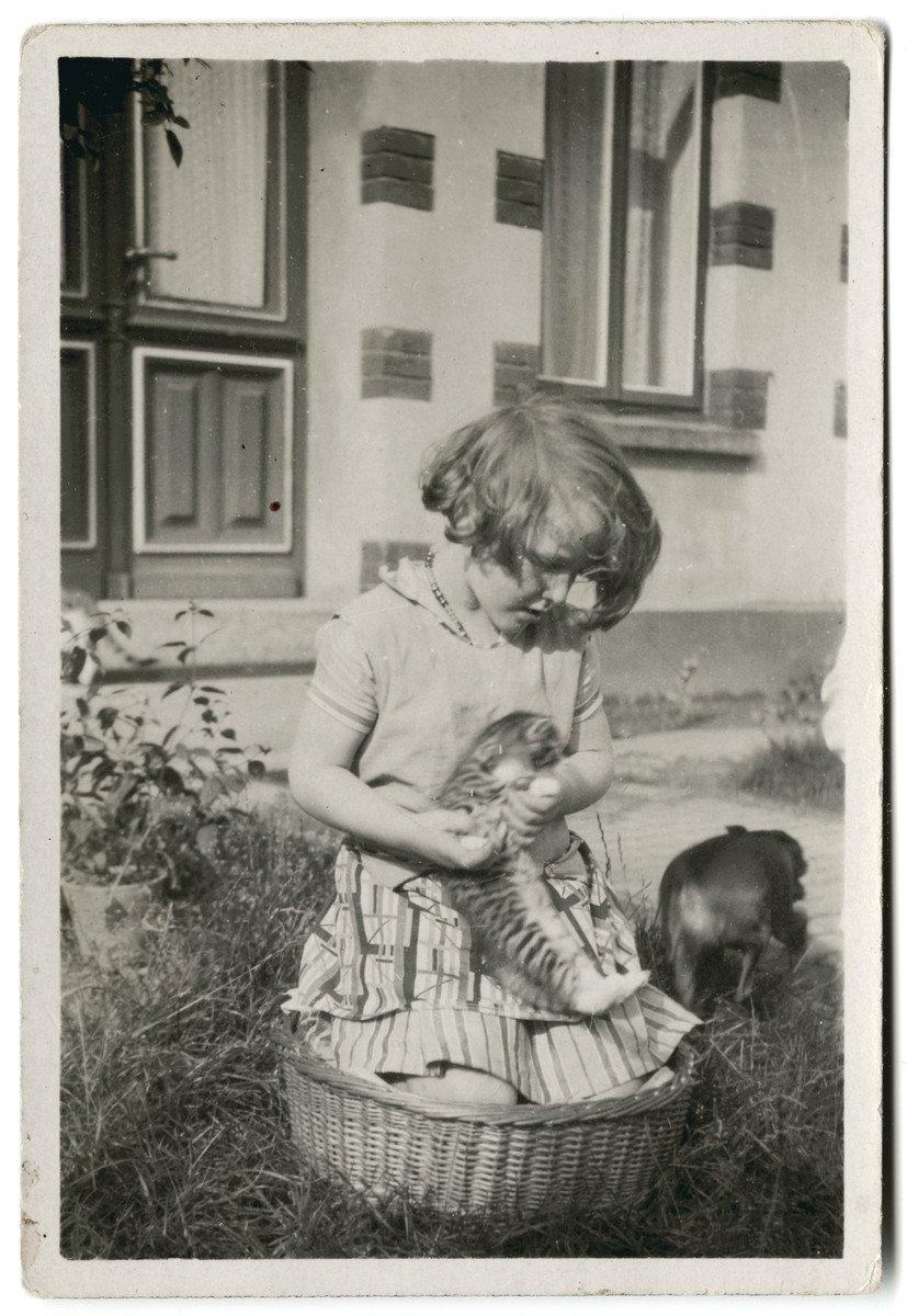 Hedwig de Levie sits in a basket and plays with a kitten near her home in Oldenburg.