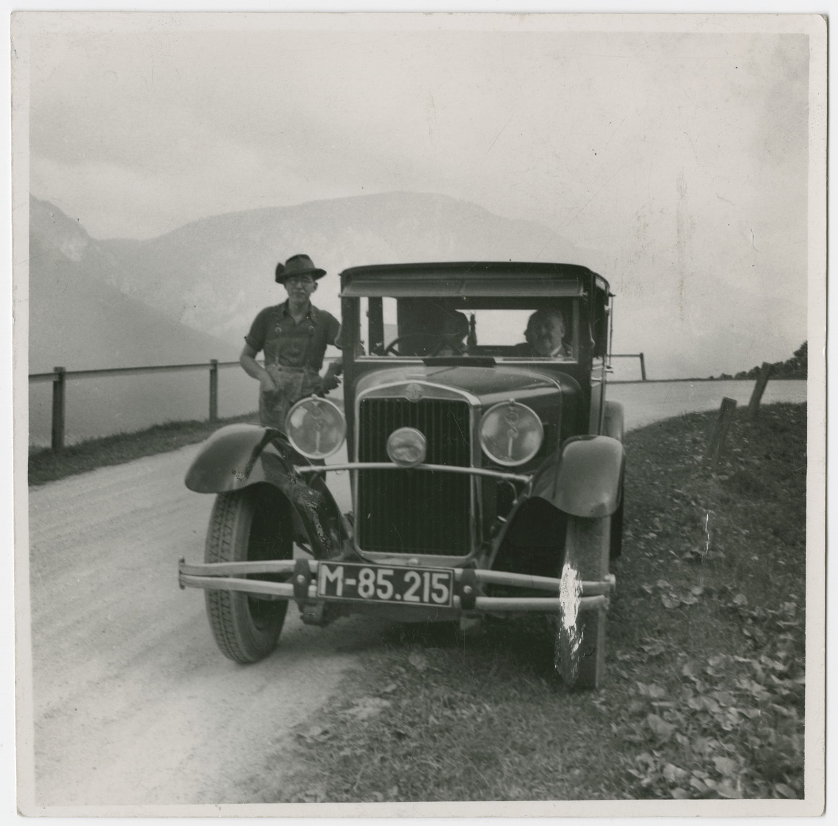 Franz stands next to an automobile parked on a country road while father Ferdinand sits inside.