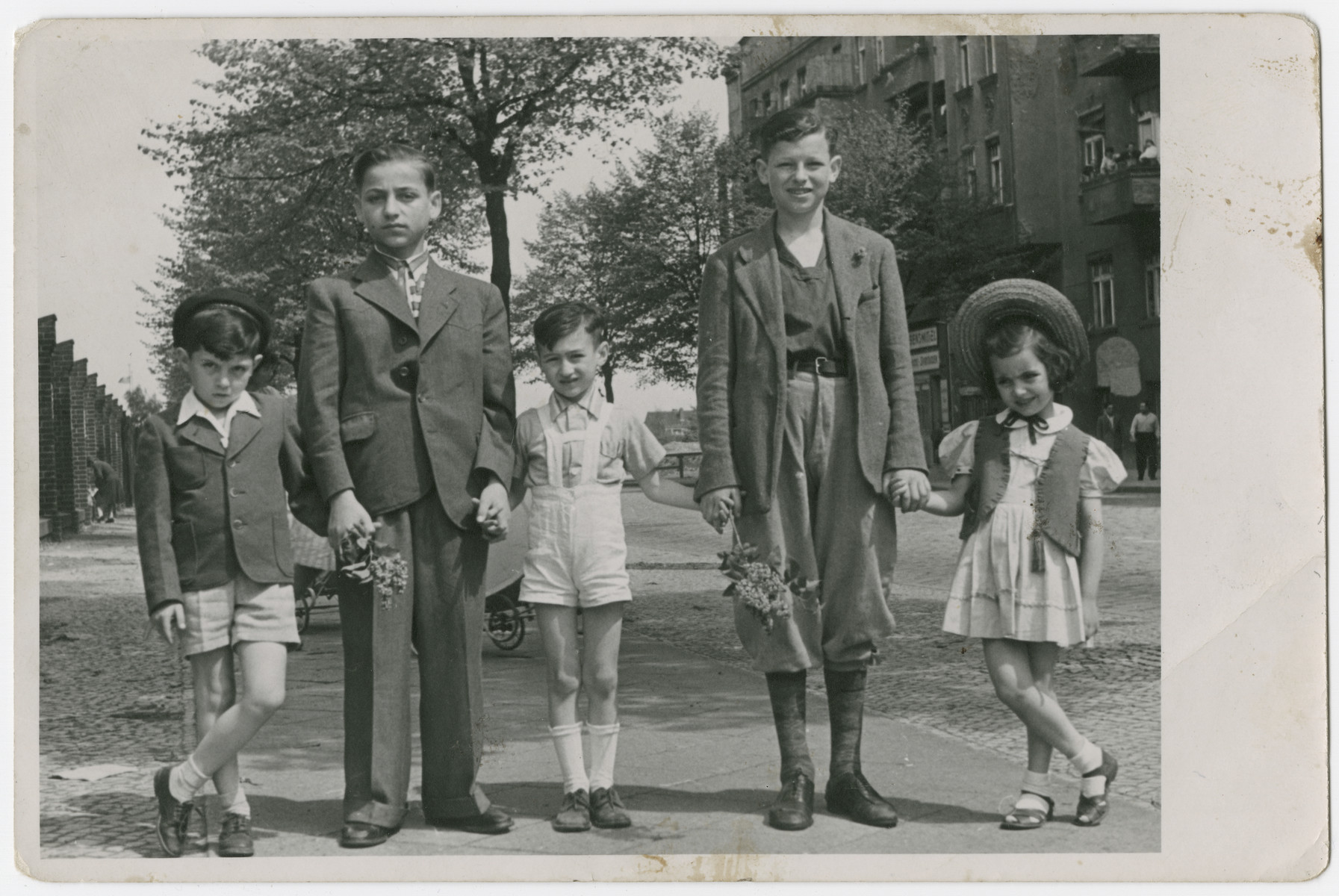 Portrait of five children from the Schlachtensee displaced persons camp holding hands.  Nathan Rubinstein is pictured second from the right.  His brother Benny is next to him in the center.
