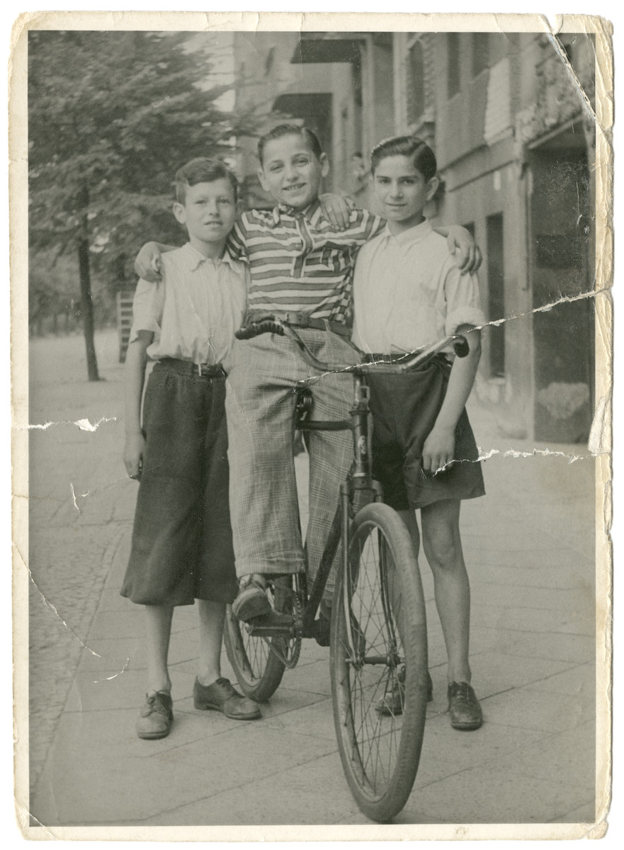 Three young Jewish friends pose by a bicycle.  Nathan Rubinstein is pictured on the left.