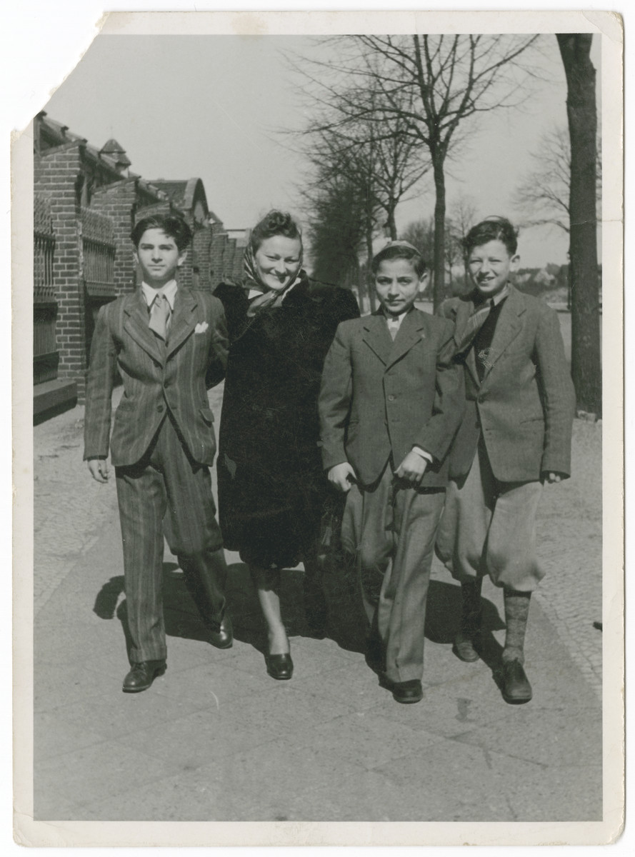 A woman and three boys walk down a street in Berlin.  Nathan Rubinstein is on the right.