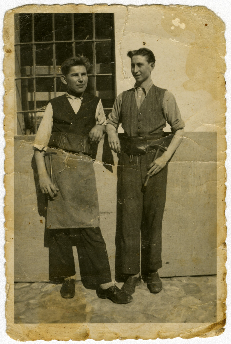 Daniel Ripp and another man pose in front of their upholstery workshop.