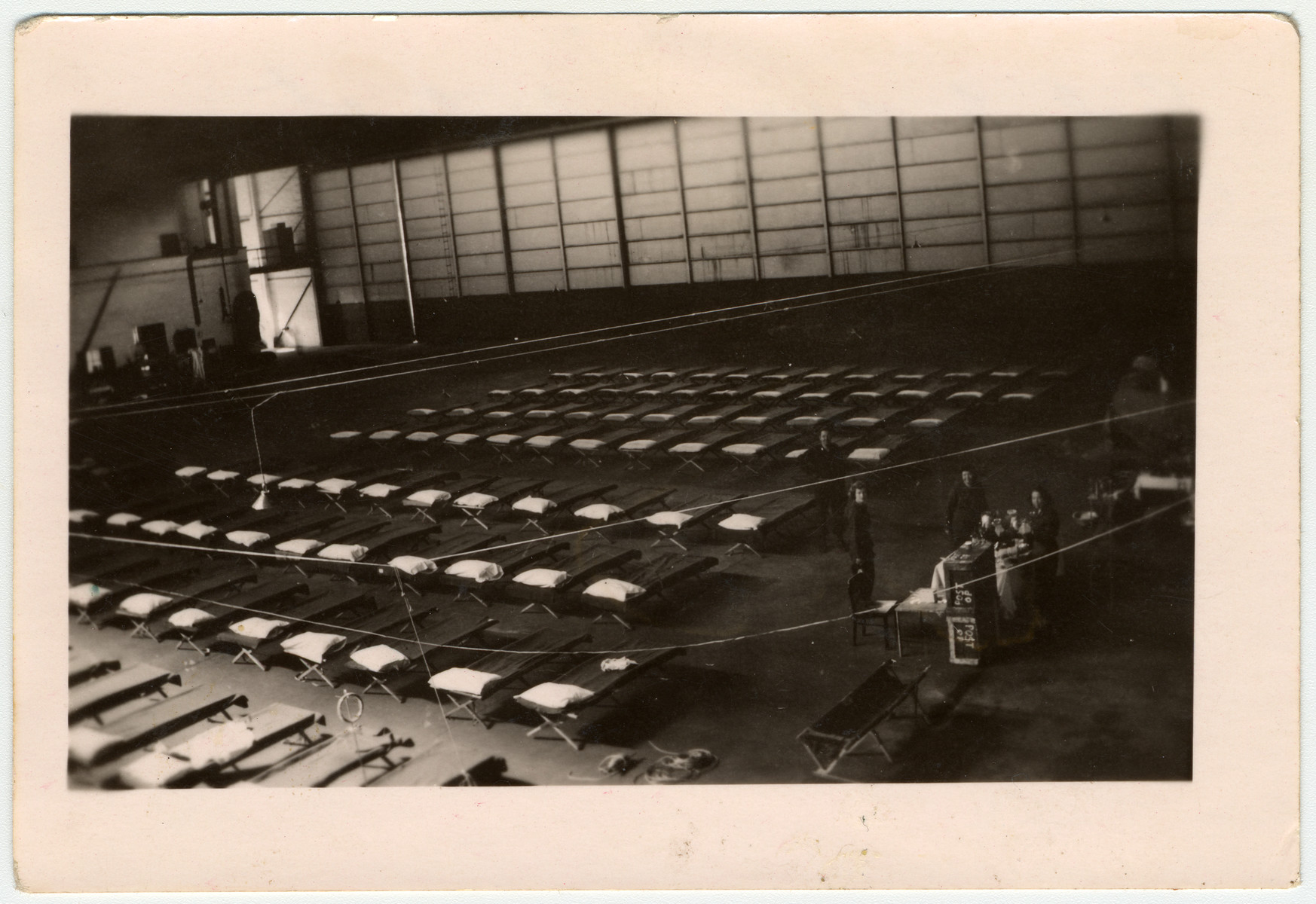 A view of the interior of an airplane hanger that was used as an infirmary for concentration camp survivors.