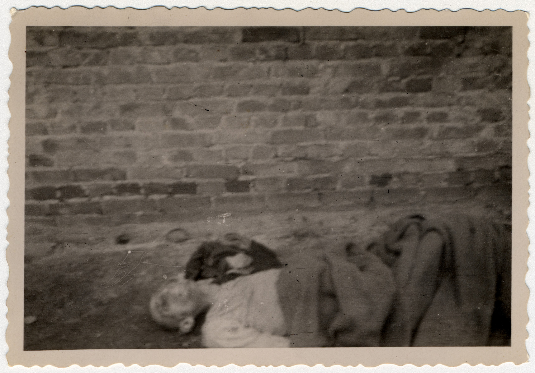 The body of a prisoner lies outside of a barrack in Woebbelin.