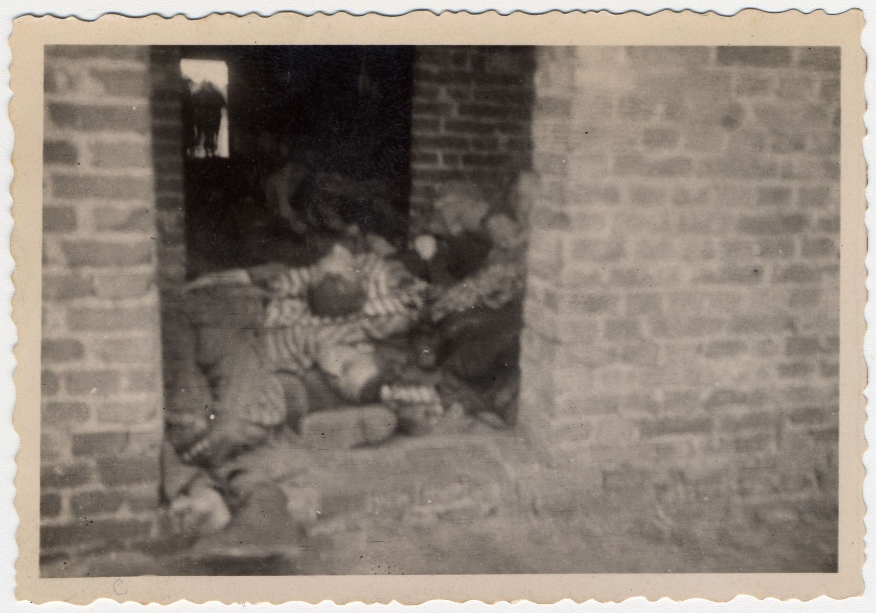 The bodies of prisoners are piled on top of one another in the doorwar of a brick barrack in Woebbelin.