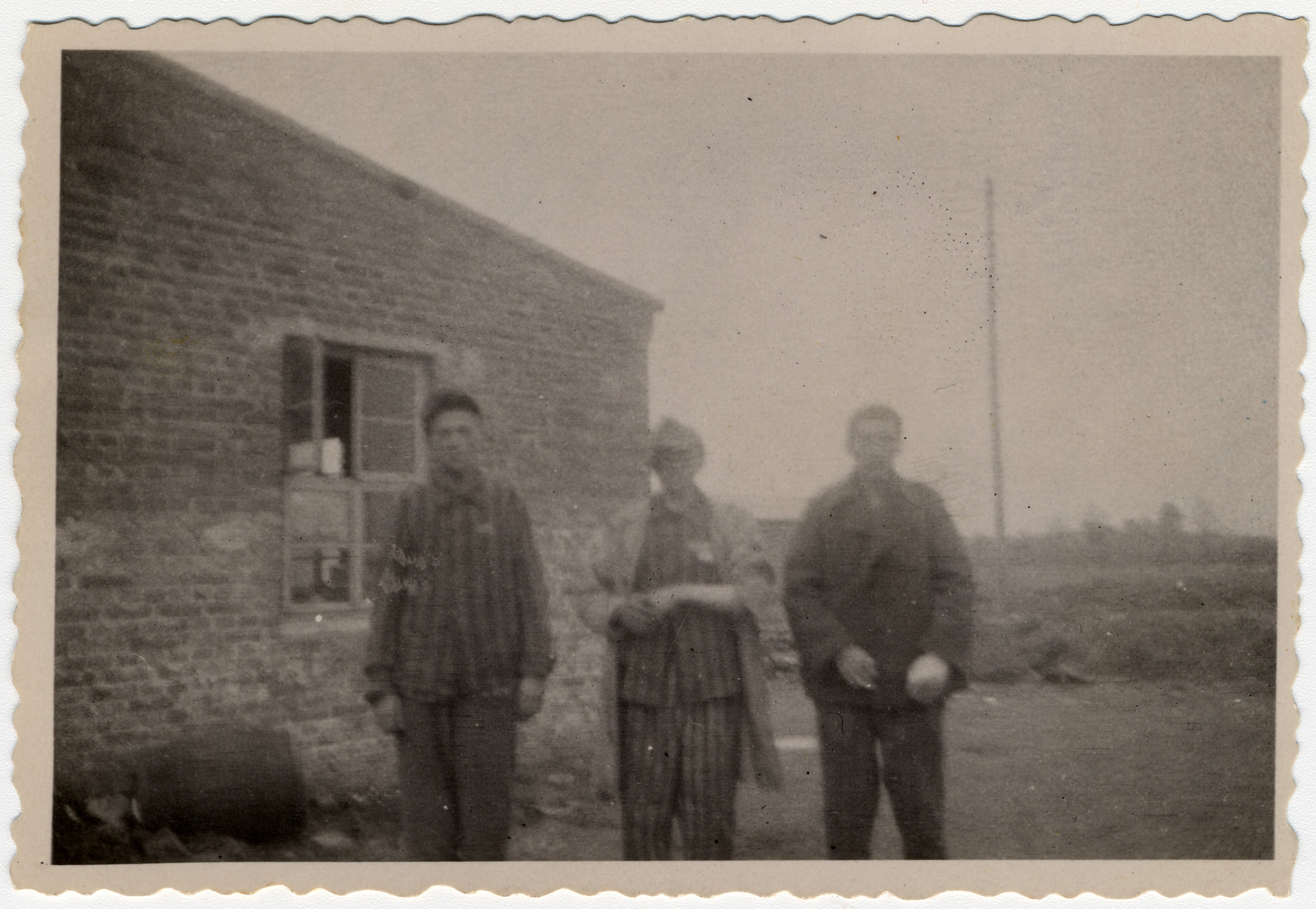Three survivors pose in front a barrack in Woebbelin.