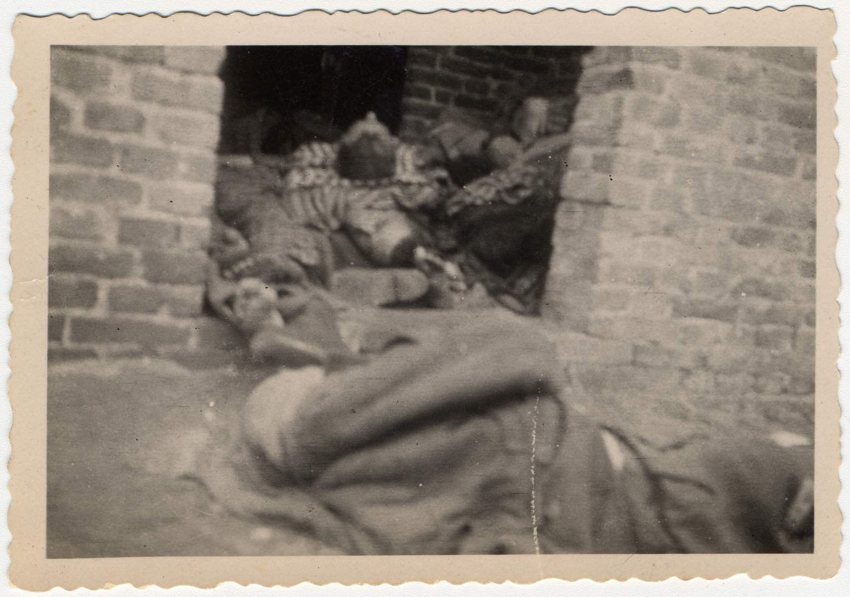 The bodies of prisoners are piled on top of one another in the doorway of a brick barrack in Woebbelin.  Original caption reads:  The concentration camp near Ludwigslust Germany.