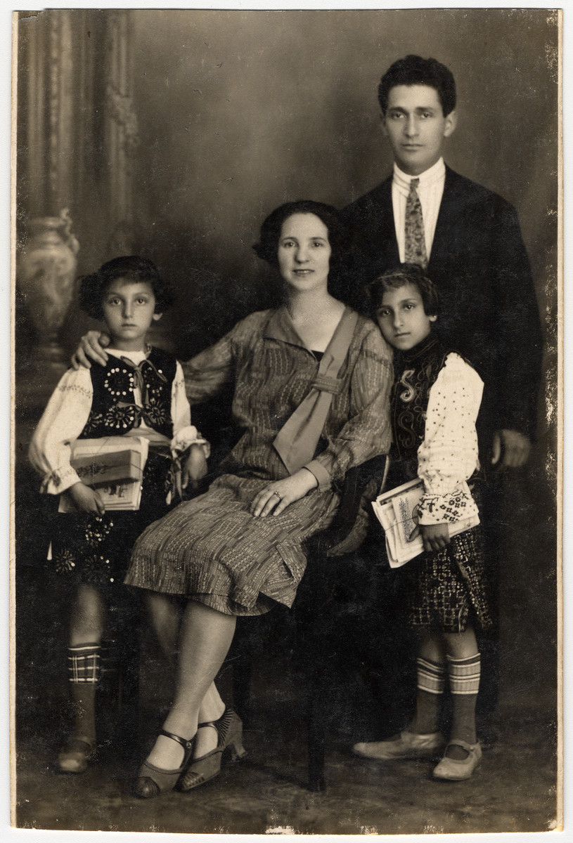 Studio portrait of a Romanian Jewish family.  Pictured are the Leibovitche family.  Herman and Lora Leibovitche and their daughters Sonya (donor's mother, right), and Golda Yvonne (left).