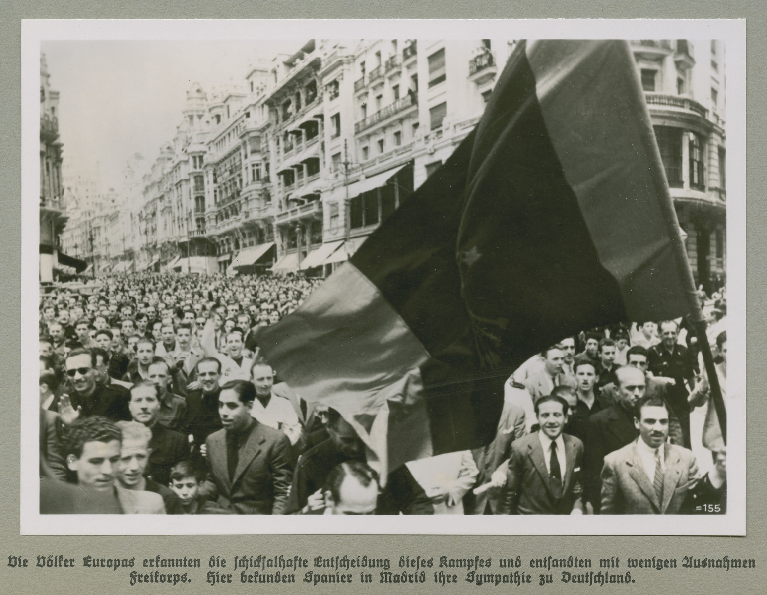 Spaniards crowd a Madrid street with a raised flag.   Original caption reads: The people of Europe recognized the fateful decision of this war and formed, with few exceptions, Freikorps. Here, Spaniards in Madrid show their sympathy for Germany.