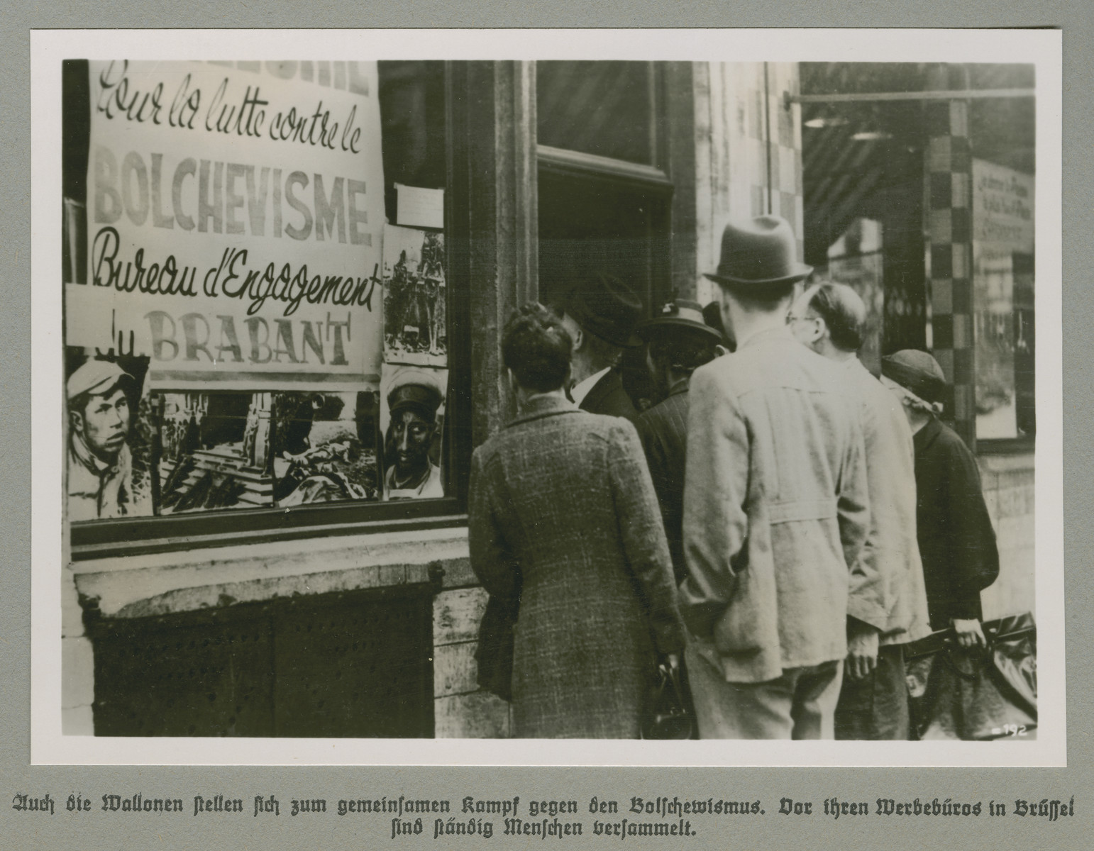Men and women view anti-Bolshevist propaganda in a storefront window.   Original caption reads: The Walloons also confront the collective struggle against Bolshevism. People are always gathered outside your (party) advertising agency in Brussels.
