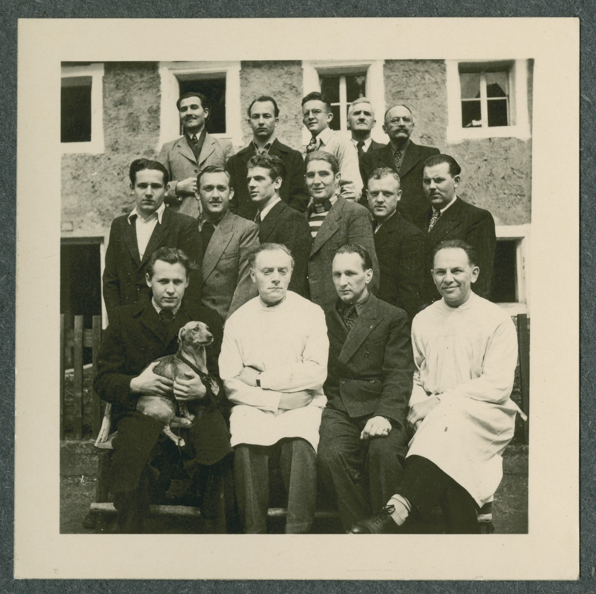 Group portrait of prisoners, one holding a small dog, in the Tittmoning camp.
