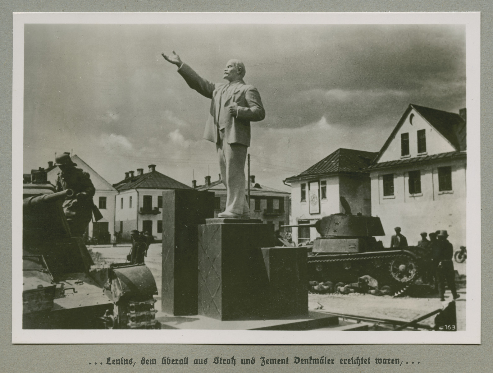 Tanks flank a statue of Lenin in a town square.    Original caption reads: ...Lenin, to whom monuments were erected everywhere made of straw and cement...