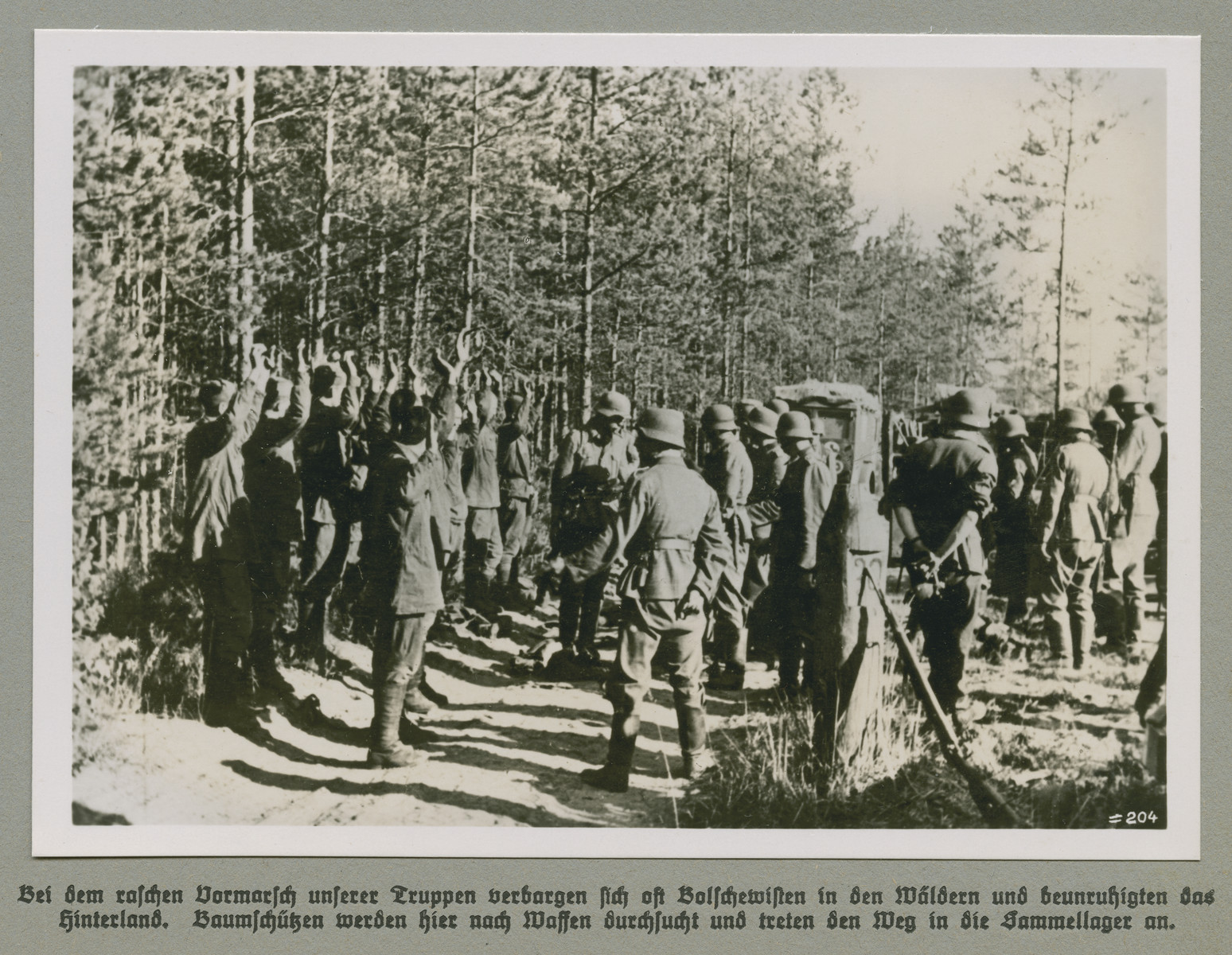 Men with their hands raised are detained by German forces.  Original Caption reads: During the rapid advance of German forces Bolshevists often hid in the forests and agitated the back country. In this image Baumschützen (forest snipers) are searched for weapons and make thier way to the detention camp.