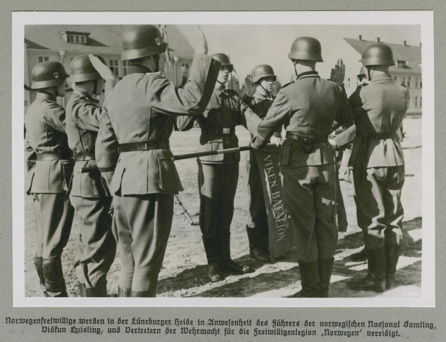 "German soldiers take an oath.  Original caption reads: Norwegian volunteers are sworn in before the leader of the Norwegian Nasjonal Samling Party, Vidkun Quisling, and representatives of the volunteer legion ""Norway"" on the Lüneburg Heath."