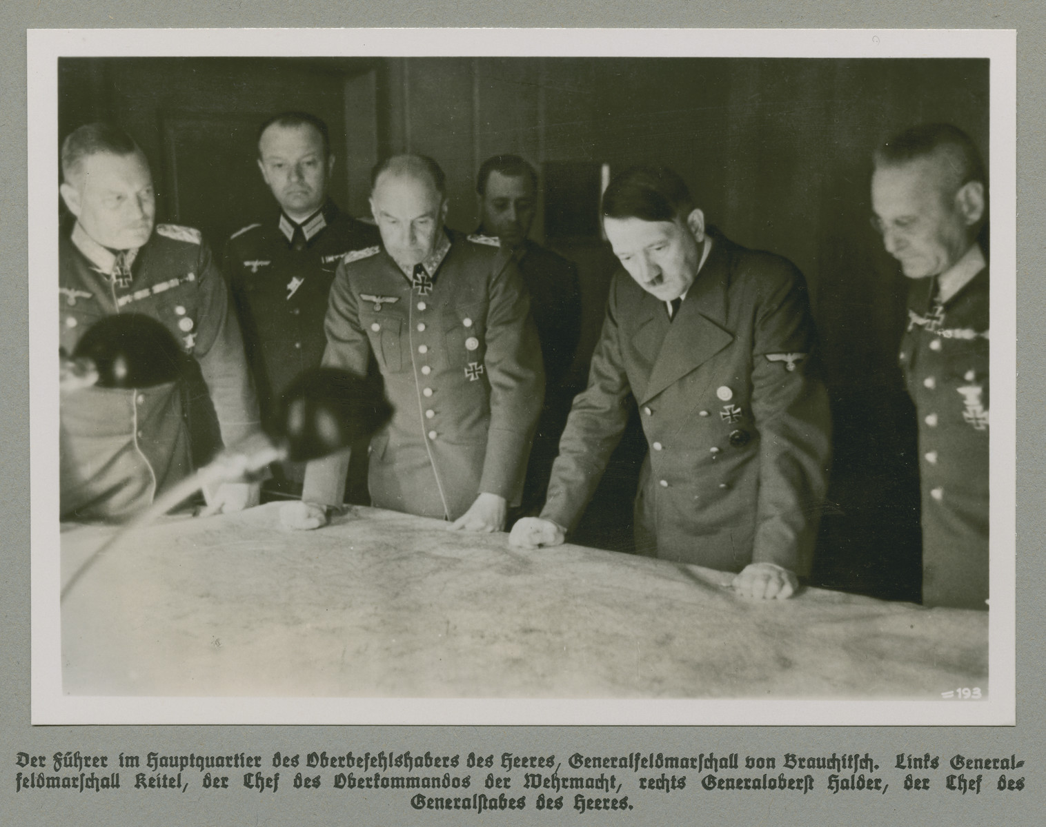 Adolf Hitler reviews military plans with his High Command.  The original caption reads: The Führer in the headquarters of Field Marshal von Brauchitsch, Commander-in-Chief of the Amred Forces.  Field Marshal Keitel, Chief of the High Command is on the left, and Colonel General Halder, Chief of General Military Staff is standing at right.