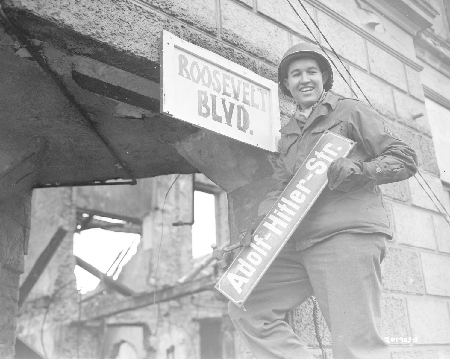 "An American soldier replaces an ""Adolf-Hitler-Str."" street sign with a hand-made one, ""Roosevelt Boulevard"".  Pictured is Sergeant George A. Kaufman of the 9th Army, from Fort Smith, Arkansas."