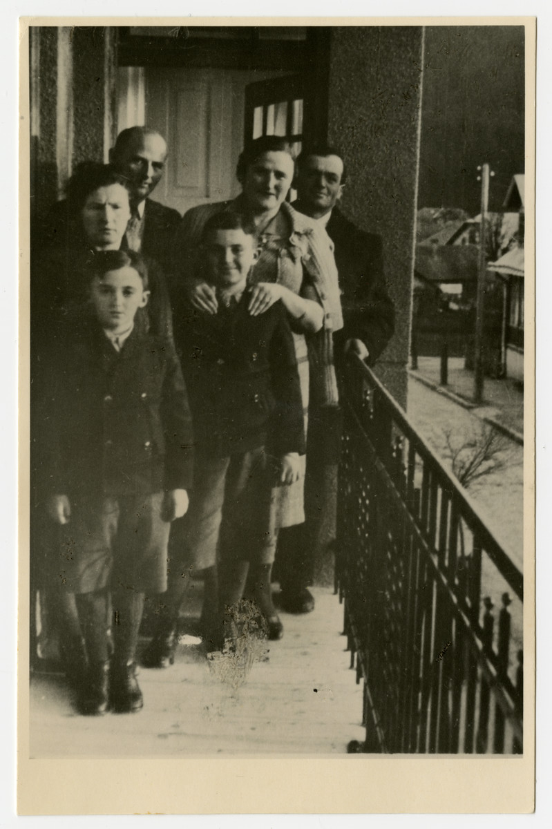 The Lieblein family poses on the balcony of its home:   Mordechai Lieblein is on the back rightt; his sister-in-law: Frieda Rozenberg Josefsberg stands in fron of him awith her hands on her nephew: Dolek Lieblein. In the back, on left stands Mocio Rozenberg, (donor's maternal uncle); in front of him is Lea Rozenberg Lieblein and first on left is Benek Dov Lieblein.;