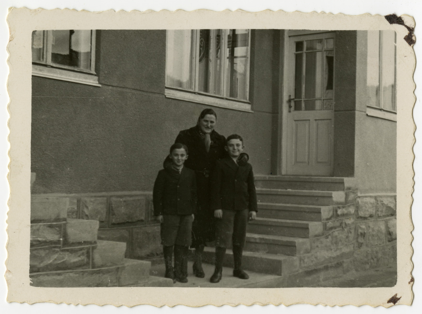 Benek Lieblein stands outside his home with his aunt Frieda Rozenberg Josefsberg and his older brother Dolek.