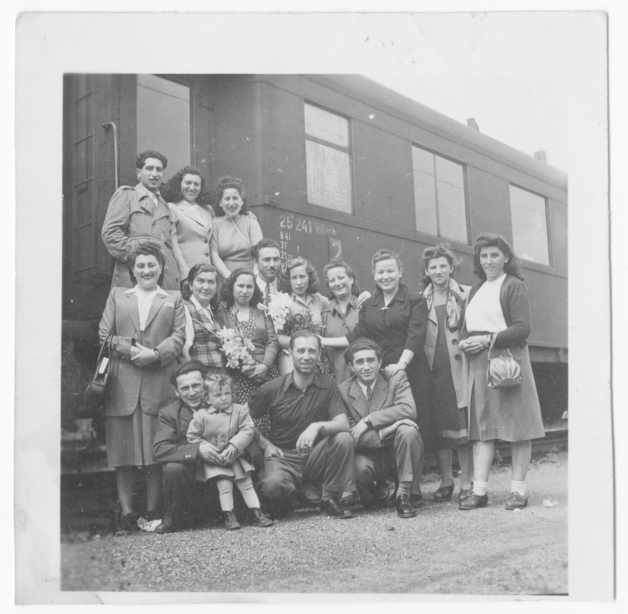 A large group of Jewish displaced persons gathers at the train station in Salzburg.    Bernard and Bella Pasternak are on the top row, first and third from the left.