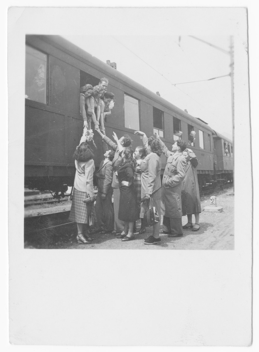 A group of Jewish displaced persons gather at the train station in Salzburg to say goodbye to their friends.