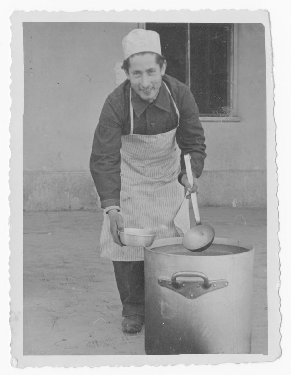 Bernard Pasternak ladles out soup in an unidentified displaced persons camp [probably in Italy.]