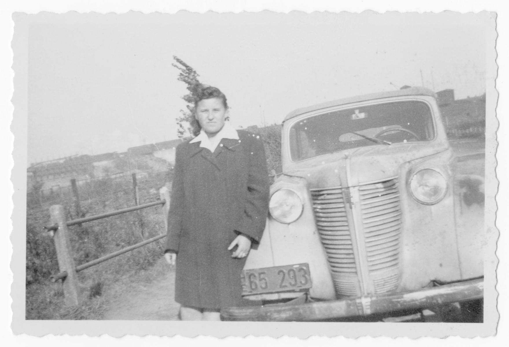 Bella Simon poses next to an automobile [possibly in postwar Romania.]