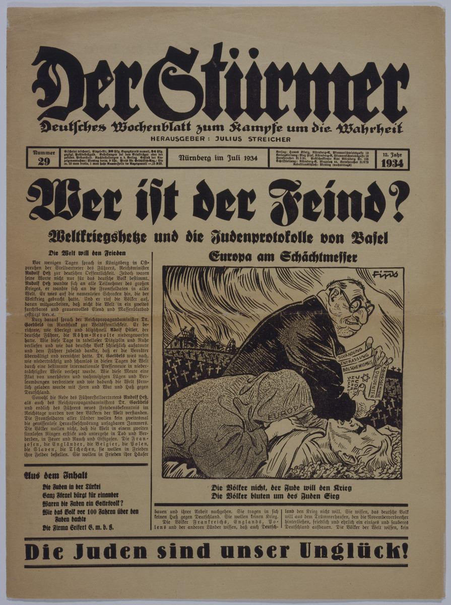 """Front page of the Nazi publication, Der Stuermer, with an anti-Semitic caricature depicting the Jew as the inciter of world war.    The headline reads, """"Who is the Enemy?/ Incitement to world war and the Jewish Protocol of Basel/ Europe at the slaughterer's knife blade.""""  The caption under the caricature reads, """"The Jew wants the war, the peoples do not/ The people bleed and the Jews are victorious."""""""