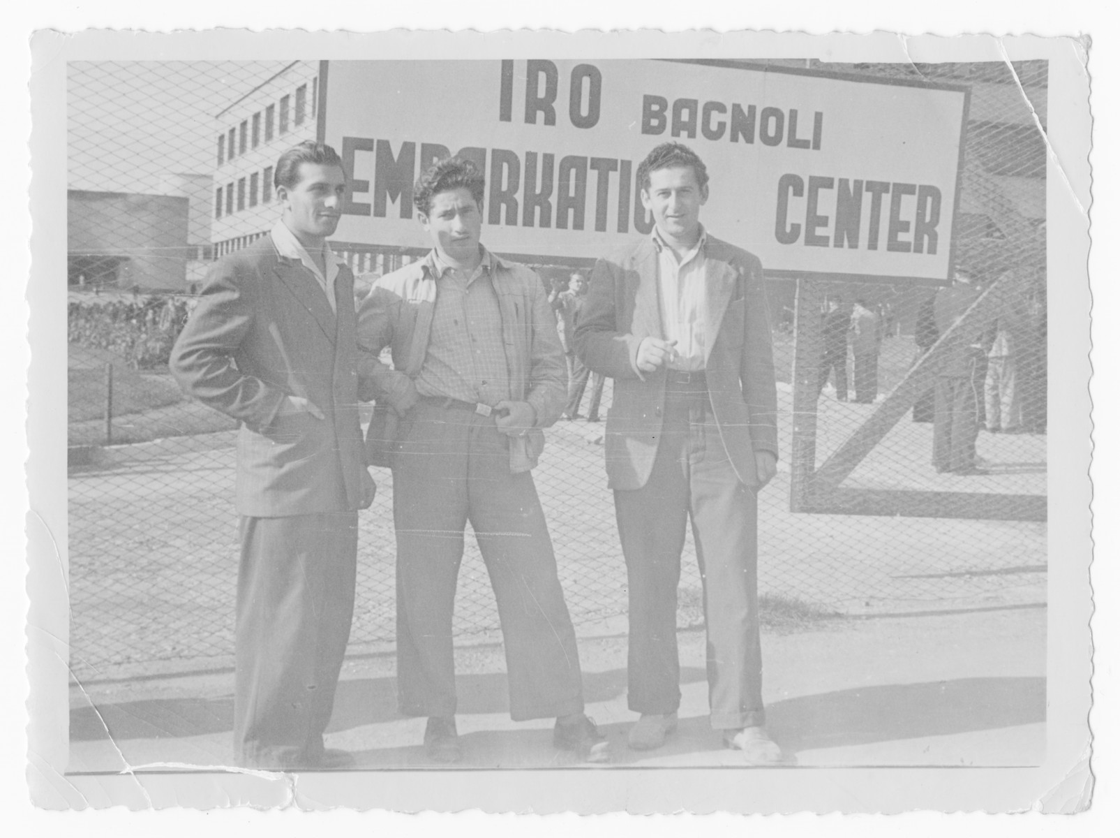 Three Jewish DPs pose in front of the sign for the IRO Embarkation Center in Bagnoli.  Bernard Pasternak is in the middle