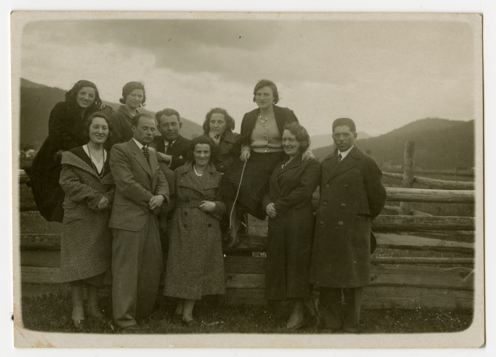 A group of Jewish family and friends stands in the Skole countryside by a fence.  Pictured standing in the first row, from left: Szajna Friedler, Beno Rozenberg, unidentified; Lotka Friedler and unidentified.  In the second row, from left: unidentified; Mania Rozenberg; Moshe Josefsberg; unidentified and Frieda Rozenberg Josefsberg.