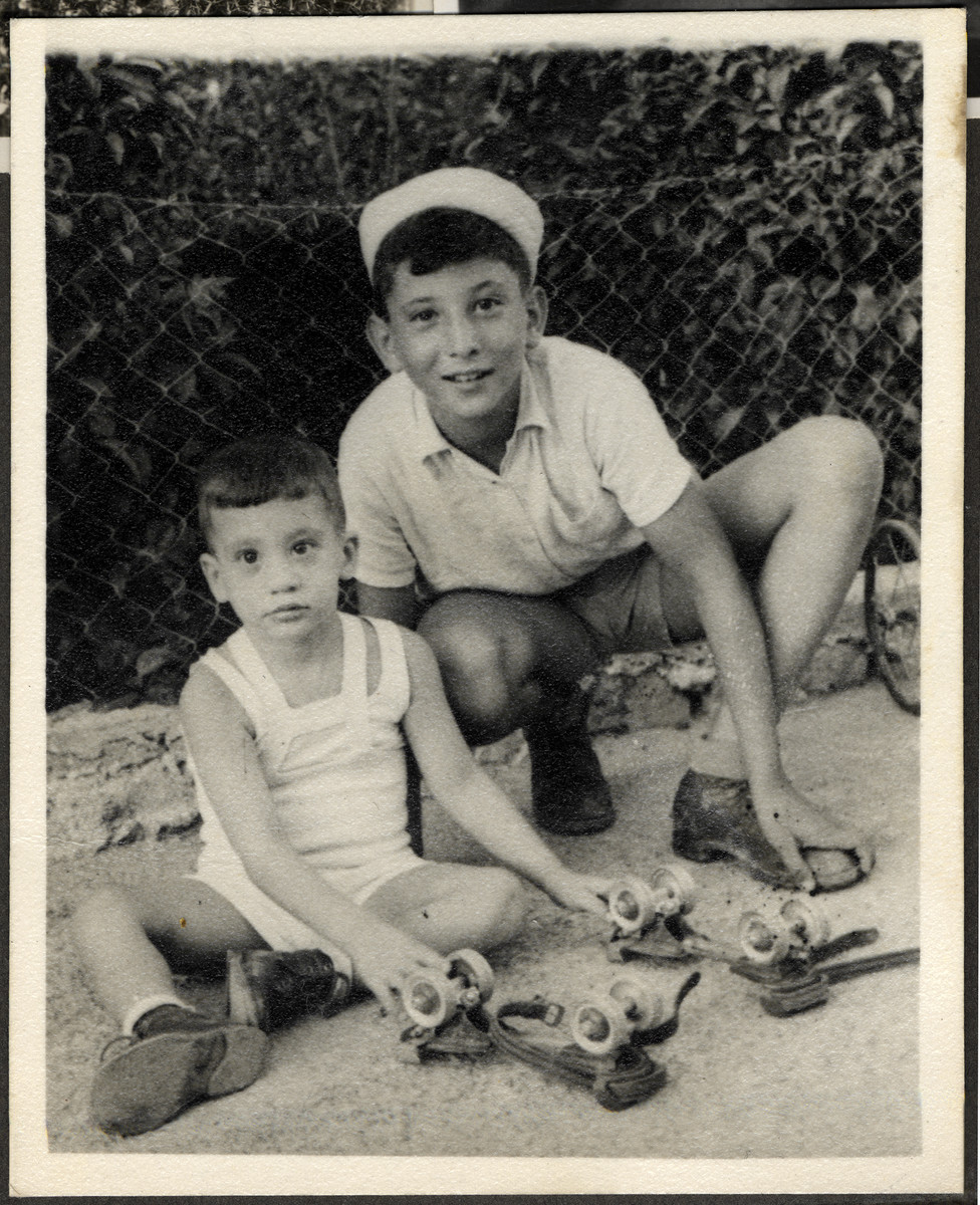 Manny Mandel poses with a younger disabled child and a pair of roller skates he received as a gift from America.   Ella Mandel was caring for the child while the family lived in Haifa shortly after settling in Israel.