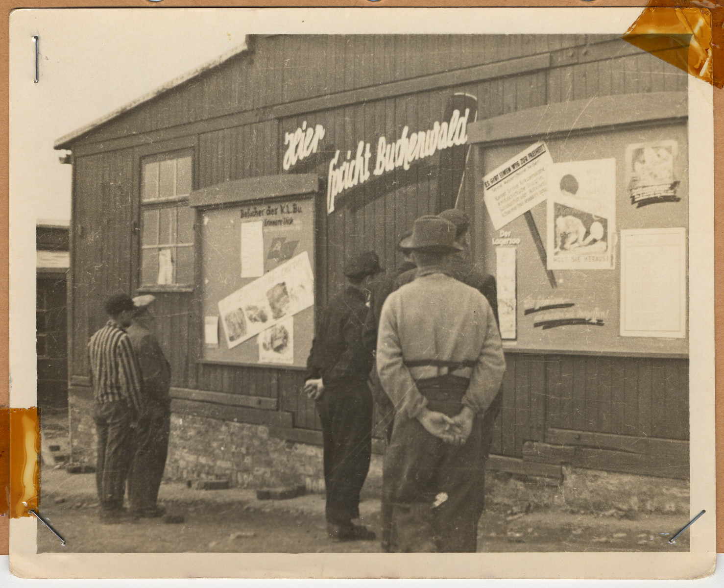 "Survivors read signs posted on the side of a building in Buchenwald.  The lender's handwritten caption reads, ""This was a Russian building."""