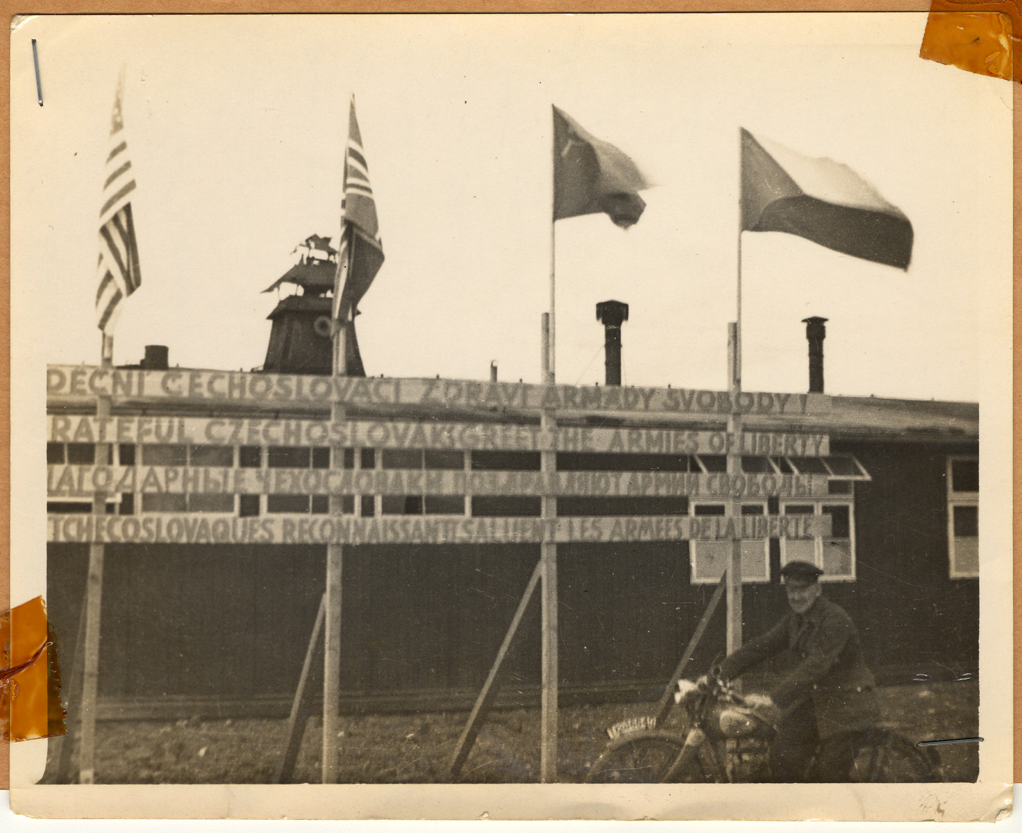 "A soldier poses on a motorcyle in front of a row of American, British, Soviet, and Czech flags.  The signs below the flags read, ""Grateful Czechoslovaks greet the armies of liberty.""  The lender's handwritten caption reads, ""The Czechs lost no time in showing us all that they stood with us in victory.  Their monuments and memorials were erected in a very short time.  In the aeiral view you can see the huge memorial to the 51,000 that died in the camp."""