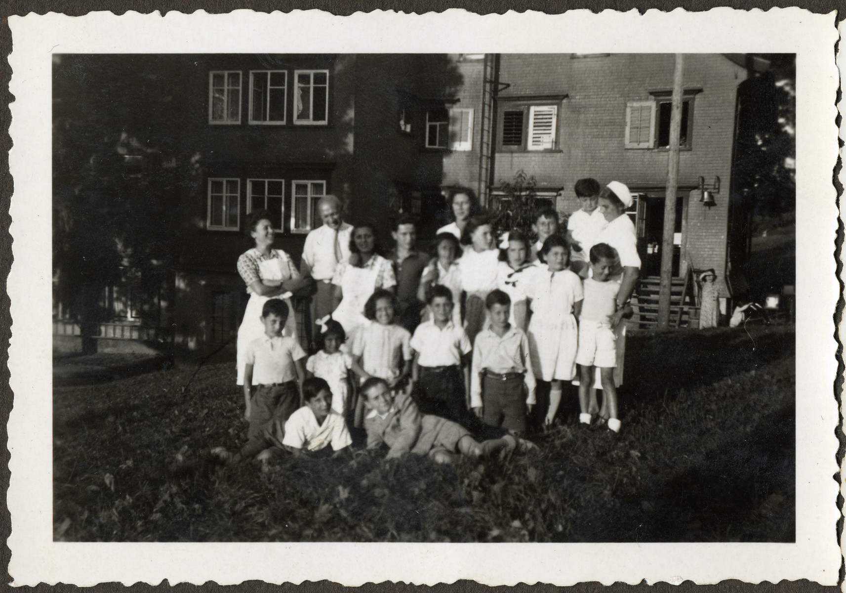 Group portrait of children and staff posing on the grounds of the Heiden children's home in Switzerland.  All of the children had been on the Kasztner Transport from Bergen-Belsen.  Manny Mandel is pictured on the bottom left.  His mother, Ella Mandel, in standing in the back row, center.  The director of the home is standing in the back left.  The boy in the arms of the nurse (right) is Ivan Fleishmann.