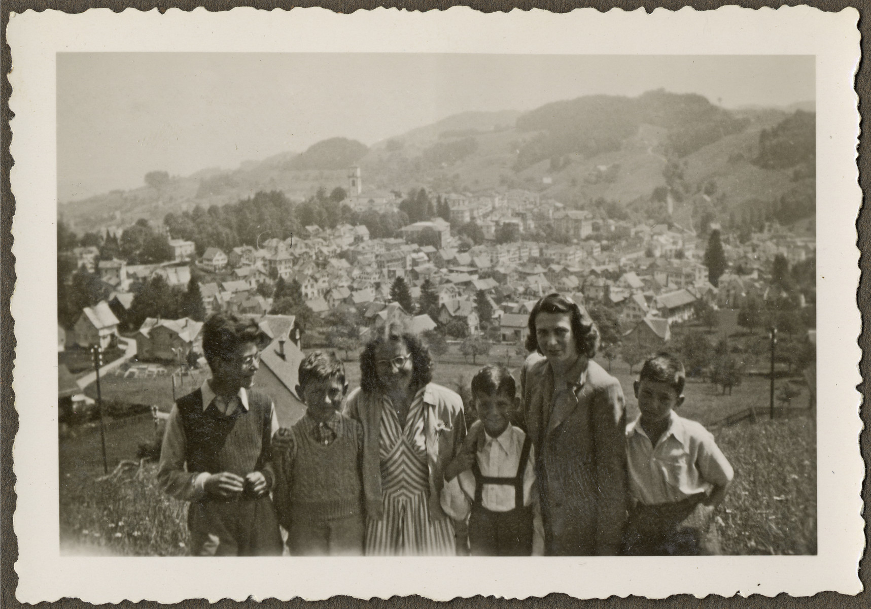 Children from the Heiden children's home and their mothers pose for a group portrait in front of view of the town.  Among those pictured is Manny Mandel (far right).