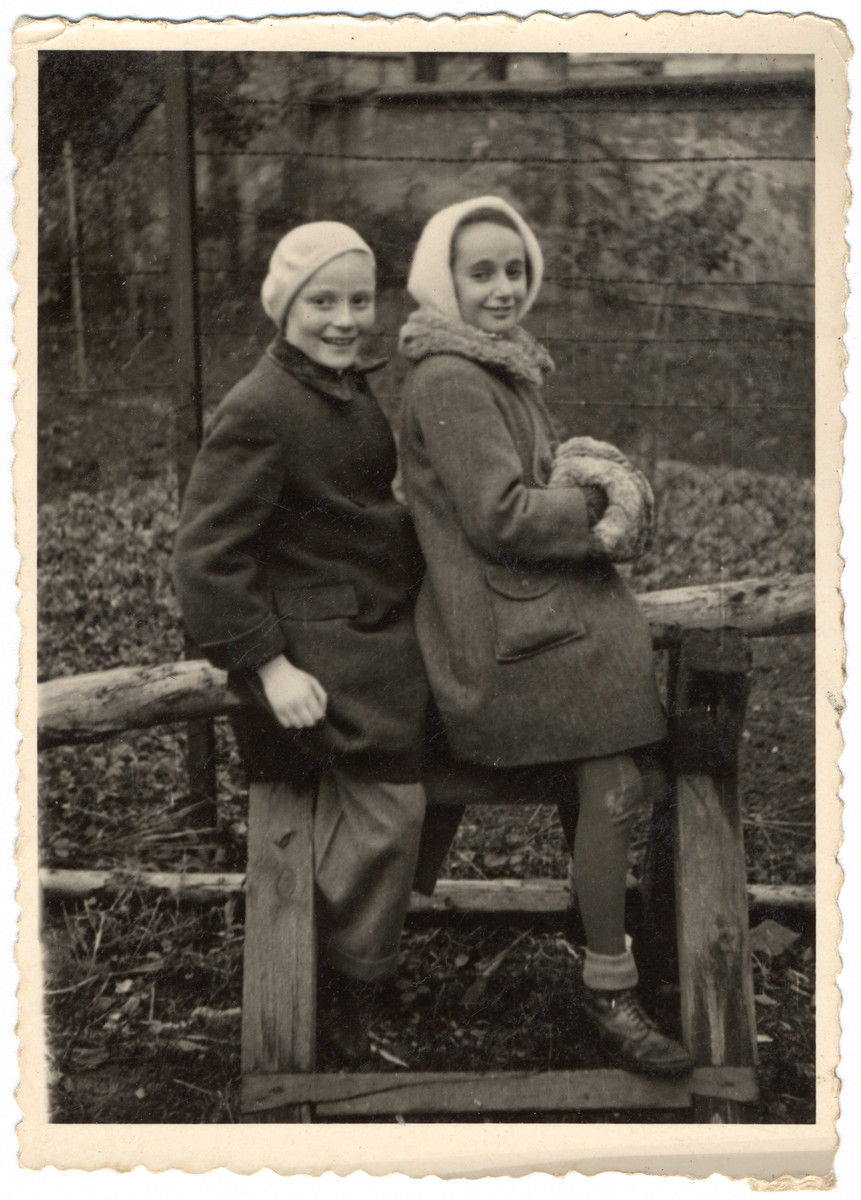 Katie and Adolph sit on a wooden fence on their uncle's estate shortly after liberation.