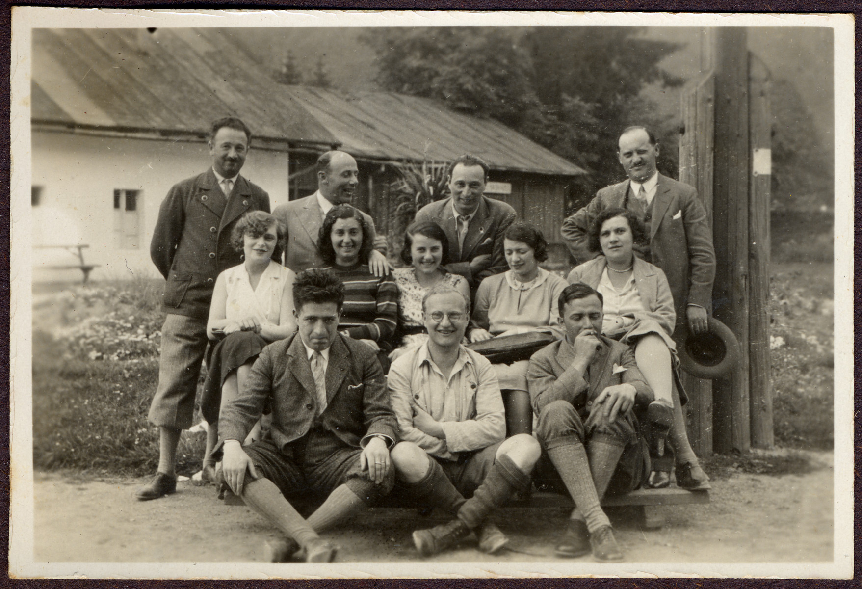 A group of Austrian Jewish friends poses for a group portrait in front of a home in the countryside.  Among those pictured is Greta Stoessler (second row, far left).