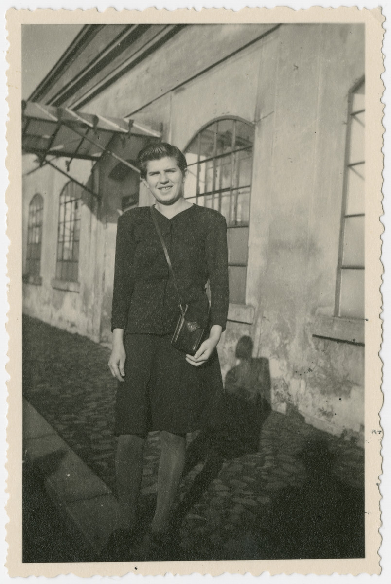 "Jolan Weinberger, a survivor of Auschwitz and a death march, poses outside a building in Varnsdorf.  The original caption reads, ""As a remembrance, Jolan."""